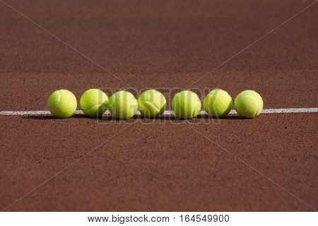 Seven yellow tennis balls in-line on court with synthetic surface in the morning front view