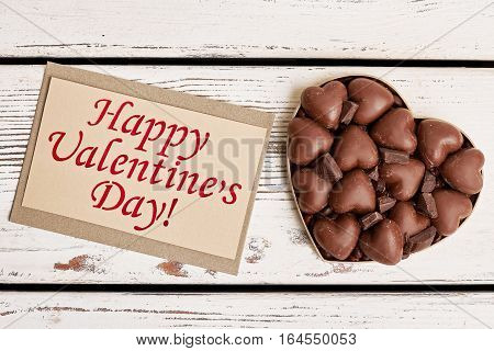 Chocolates on Valentine's Day. Sweets near greeting card. Spend this day with beloved.