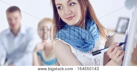 Young woman drawing on wihteboard with white copyspace, isolated