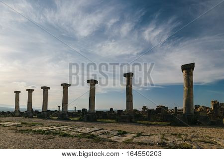 Seven columns at Volubilis on a sunny day with blue sky and few clouds , Morocco.