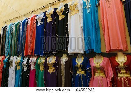 Multicolored clothes on a souk in Fez, lined up on a wall in Morocco.