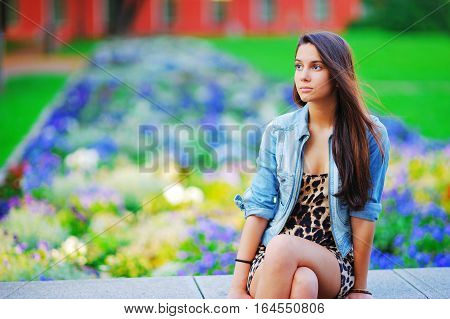 young woman cute brunette girl sitting on bench in leopard dress on summer outdoor