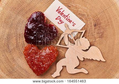 Heart-shaped toast with jam. Valentine's Day card near Cupid. Delicious romantic breakfast for beloved.