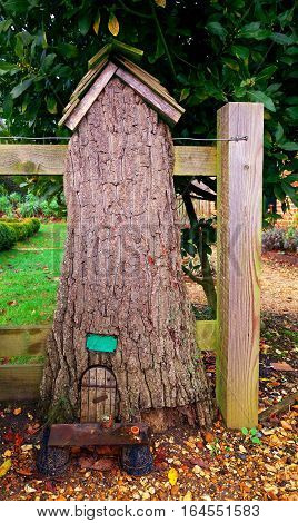 Fairy door in a tree trunk with autumn leaves on the ground in front of the entrance. With space for text. The little potting shed is closed at lunch.