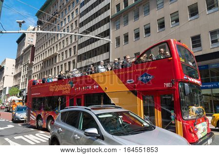 NEW YORK - APRIL 30 2016: Double decker tourist bus with open roof in the streets of downtown manhattan.