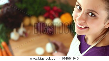 Young woman cutting vegetables in the kitchen .