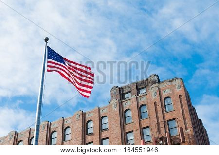 US flag waving in the wind against blue sky