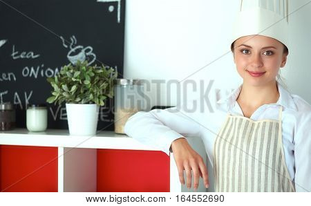 Chef woman portrait with uniform in the kitchen .
