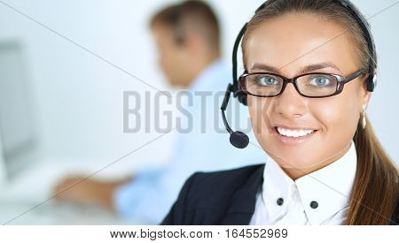 Happy female wearing headset and sitting on the desk .