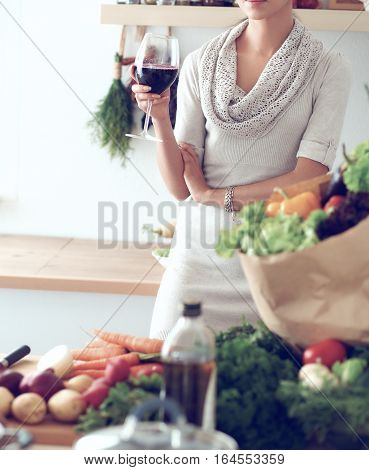 Young woman cutting vegetables in kitchen, holding a glass of wine .