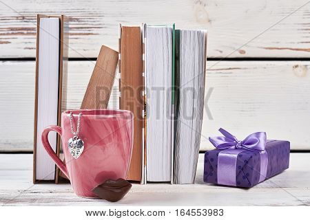 Books, cup and gift box. Heart-shaped pendant and chocolate. Book is a wonderful present.
