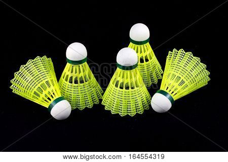 Five yellow badminton shuttlecocks with white cork isolated on black