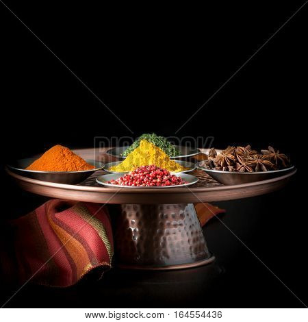 Colorful variety of spices on a copper presentation platter.