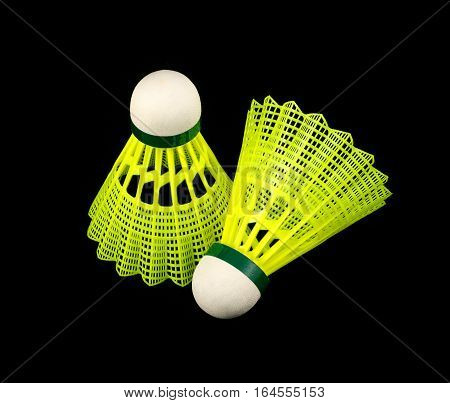 Two yellow badminton shuttlecocks with white corks isolated on black indoor