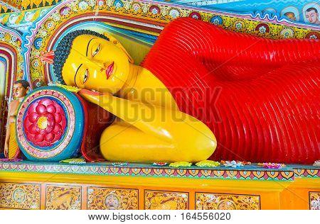 ANURADHAPURA SRI LANKA - NOVEMBER 26 2016: The Reclining Buddha in Isurumuniya Rock Temple surrounded by painted and carved lotus flowers on November 11 in Anuradhapura.