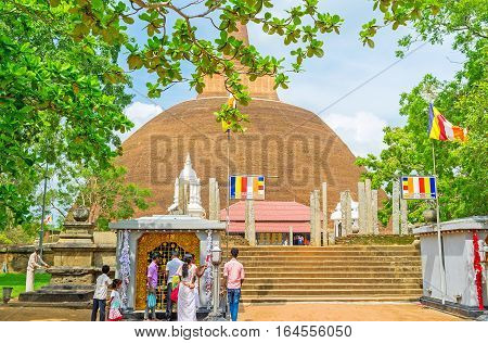 ANURADHAPURA SRI LANKA - NOVEMBER 26 2016: The massive brick Abhayagiri Stupa with preserved vatadage pillars in front of it on November 26 in Anuradhapura.