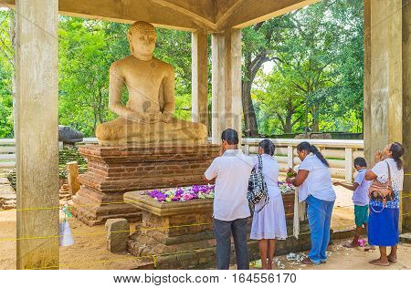 ANURADHAPURA SRI LANKA - NOVEMBER 26 2016: The Buddhist worshipers pray at Samadhi Buddha Statue located in Mahamevnawa Park of Sacred City on November 26 in Anuradhapura.