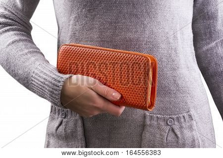 woman holds an orange purse in hands