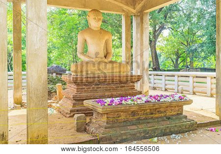 The meditating Samadhi Buddha Statue with the colorful lotus flowers on the altar Anuradhapura Sri Lanka.