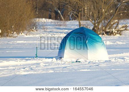 Landscape with Fisherman color tent on frozen river and brown trees behind