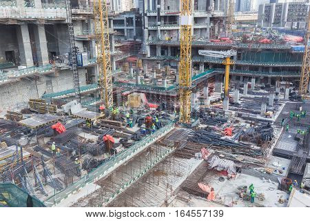 Laborers working on modern construction site works in Dubai. Fast urban development concept.