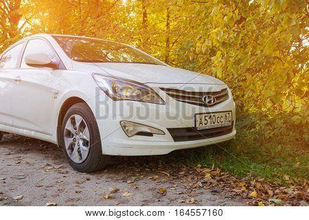 Smolensk, Russia - October 01, 2016: New Hyundai Solaris in sunlight. Modern korean car parked in a beautiful autumn forest.