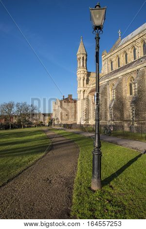 A pathway in Verulamium Park running alongside the historic St. Albans Cathedral in the city of St. Albans England.