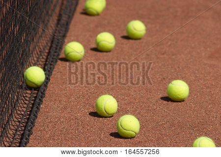 Ground court with many yellow tennis balls before net closeup