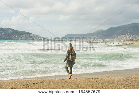 Young woman traveler walking on sandy beach and looking at stormy Mediterranean sea in winter in Alanya, Turkey.