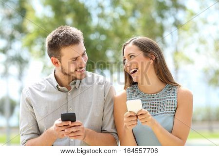 Front view of a couple or friends joking and using smart phones on line outdoors in a park