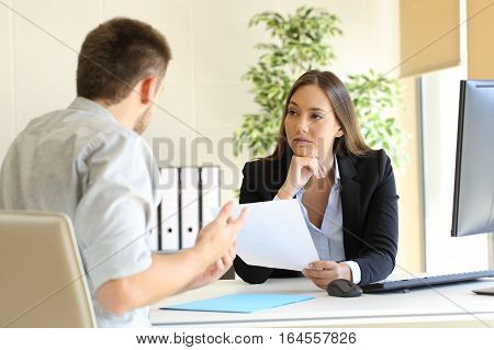 Man searching employment in a bad job interview with the interviewer looking mistrustful