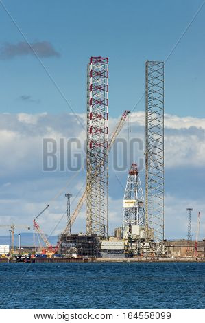 Balnapaling Scotland - June 3 2012: Galaxi Z petroleum and national gas drill platform under construction in the harbor. Tall frames and cranes. Heavy metal contraption. North Sea in front under blue cloudy sky.