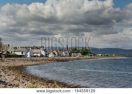 Cromarty Scotland - June 3 2012: The historic fishing and trading village on the North Sea bay under heavy loaded cloudy sky. Shot from distance. Hills in background. Rocky shore.