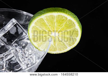 Sparkling Beverage In A Martini Glass With A Lime Slice On A Black Background