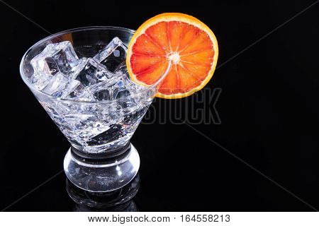 Sparkling Beverage In A Martini Glass With A Blood Orange Slice On A Black Background