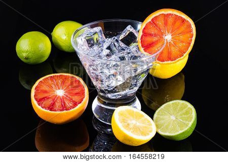 Sparkling Beverage In A Martini Glass With Colorful Citrus On A Black Backgorund