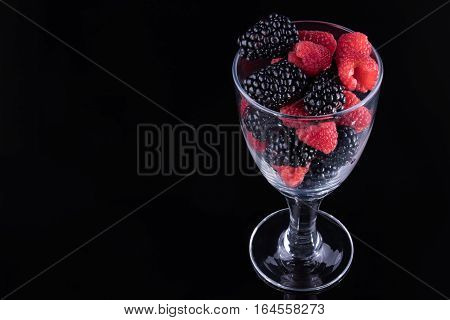 Blackberries and raspberries in a stemmed glass