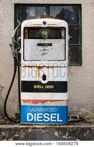 Dornoch Scotland - June 3 2012: Closeup of an antique mainly white gas pump. labeled Shell and Diesel. It stands in the street near a workshop and is still used to fuel trucks and tractors.