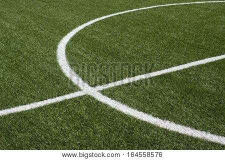 The center part of a soccer field with green synthetic grass and white lines on it closeup