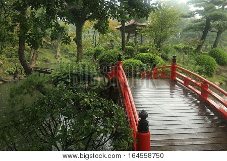 Red Japanese bridge in a rainy garden setting