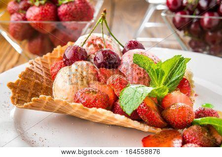 Banana split sundae ice cream in a bowl with strawberry and raspberry vanilla icecream scoops