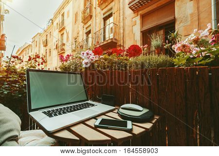 Cozy beautiful workspace on balcony with laptop smartphone wooden fence and a lot of flowers sunny summer day historical district of Barcelona - El Born with facades of houses in background