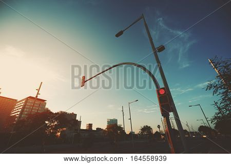 Wide angle shot of red traffic light on street lantern near highway sunset and evening in residential Forum district of Barcelona Spain clear sky and distant spindrift clouds