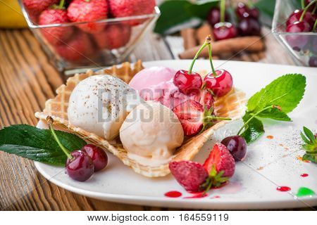 Banana split sundae ice cream in a bowl with strawberry and raspberry vanilla icecream scoops