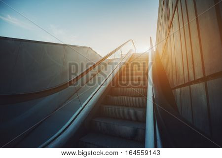 City street outdoor grungy modern escalator goes up to sun and blue sky rusty metal tiled wall on the right view from the rail Barcelona Spain