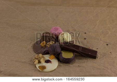 Composition of chocolate candies and dried oranges on a crumpled paper. focus on distant objects. sweets lie on paper