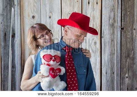 horizontal image of  woman standing behind her man who is wearing cowboy hat and red tie with little white hearts embracing him holding  teddy bear with a valentine heart that says