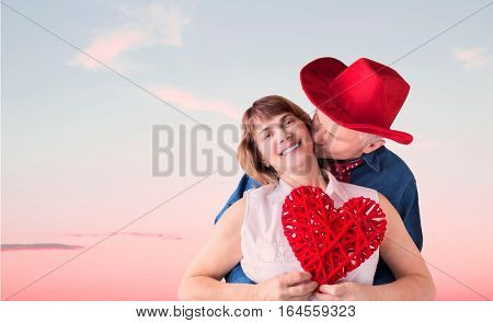 horizontal image of a cowboy wearing a red cowboy hat embracing his lady love who is holding a big red heart for valentines day with a sunset in the background.
