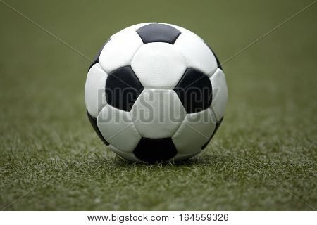 Classic ball for playing soccer in white with black accents on artificial turf, close-up view