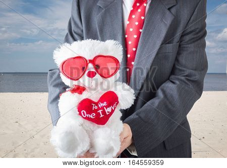 horizontal image of a torso of a man holding a white teddy bear with valentine shaped sunglasses and a little red heart that says